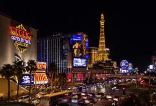 Das Bild zeigt eine Straße mit dichtem Straßenverkehr, hohe Gebäude und Casinos in Las Vegas bei Nacht.