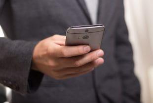 Ein Mann hält ein Smartphone in der Hand.