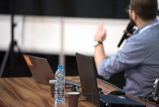 Mann mit Mikrofon spricht; im Vordergrund Schreibtisch und offener Laptop.