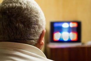 Ein Mann verfolgt von der heimischen Couch eine TV-Show.