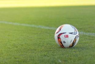 Ball mit Bundesligalogo auf Fußballplatz.