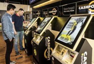 Zwei Männer stehen vor einem Sportwettenautomaten im Merkur-Wettbüro Cashpoint