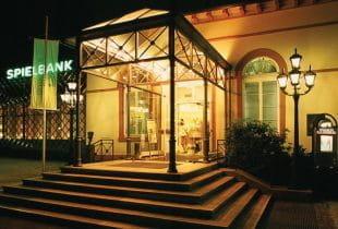 Der schön beleuchtete Eingang der Spielbank Bad Homburg bei Nacht.