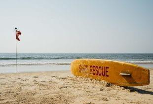 Surfbrett und Flagge an einem Strand in Goa