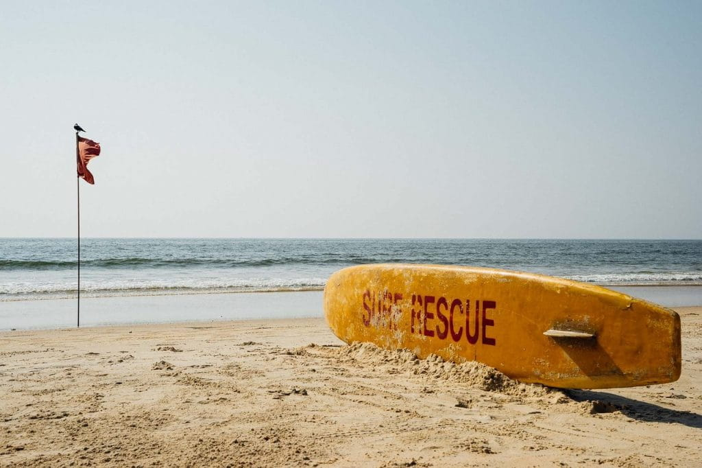 Surfbrett und Flagge an einem Strand in Goa..