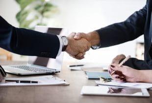 Zwei Geschäftsmänner reichen sich die Hände nach beschlossenem Deal.