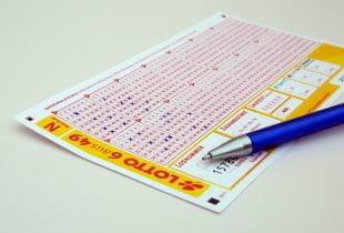 """Ausgefüllter Lottoschein des deutschen """"6 aus 49"""" mit draufliegendem Stift"""