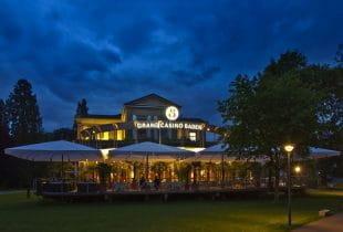 Das beleuchtete Grand Casino Baden bei Dämmerung.