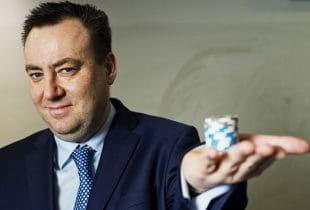 Kenny Alexander, CEO von GVC Holdings, mit einem Stapel Pokerchips in der gehobenen Handfläche