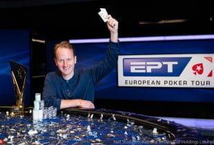 Der Gewinner des Main Event der EPT 2019 in Barcelona Simon Brandstrom am Siegertisch inklusive Pokal und seiner Siegerhand.