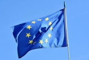 EU-Flagge im Wind vor blauem Himmel.