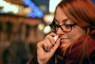 Eine Frau nimmt Nasenspray.