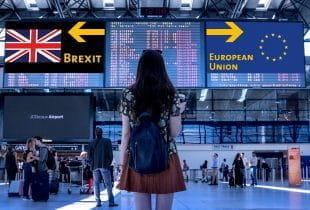 : Frau am Flughafen befindet sich vor Bildschirmen mit den Kennzeichnungen Brexit und European Union.