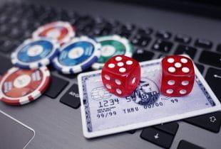 Jetons, Würfel und Kreditkarte auf einer Laptop-Tastatur.