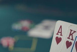 Die Pokerkarten Ass Herz und König Herz werden vor einem Pokertisch gehalten.