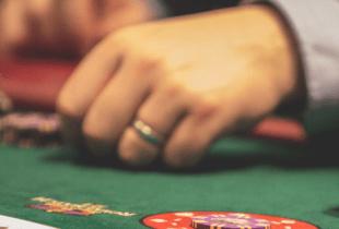 Mehrere Männer spielen an einem Tisch Poker.