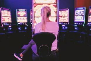 Erwachsene Frau sitzt vor einem Spielautomaten.