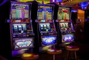 Grell und bunt blinkende Spielautomaten nebeneinander in Spielhalle.