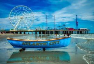Ein blaues Boot mit der Aufschrift Atlantic City an einer Küste vor einem Hintergrund eines Stegs mit Freizeitparkattraktionen.