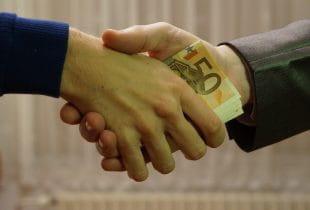 Mit einem Handschlag zweier Männer werden 50-Euro-Scheine übergeben.