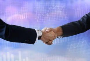 Handschlag zweier Männer vor Diagrammen.
