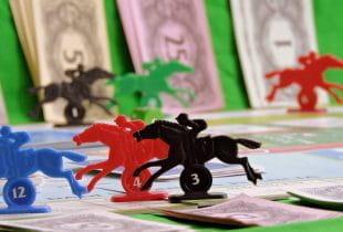 Reitsportler als Spielfiguren auf grünem Tisch; im Hintergrund Spielgeld.