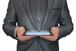 Ein Mann in einem Nadelstreifenanzug hält ein Tablet in seinen Händen.