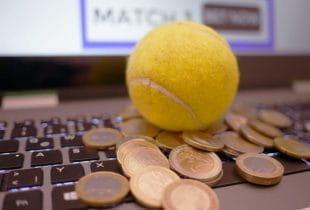 Ein Tennisball sowie verschiedene Geldmünzen liegen auf der Tastatur eines Laptops.