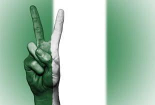 Flagge Nigerias; im Vordergrund Hand mit Peace-Zeichen und grün-weißen Fingern.