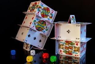 Kartenhäuser kurz vor dem Umfallen; daneben bunte Würfel.