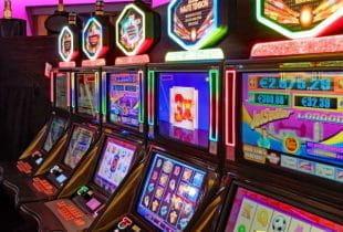 Mehrere Bildschirme von Spielautomaten nebeneinander.
