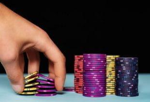 Eine Hand greift in mehrere Stapel von Pokerchips.