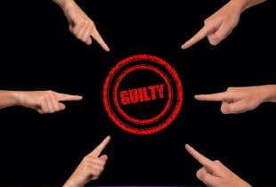 Sechs Finger zeigen in Kreisform auf einen Sticker mit der Aufschrift guilty.