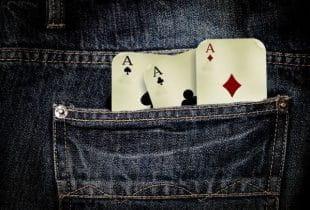 Die hintere Tasche einer Jeans, aus der drei Ass-Spielkarten herausgucken.