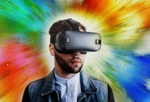 Ein Mann trägt eine VR-Brille vor einem bunten und farbenfrohen Hintergrund.