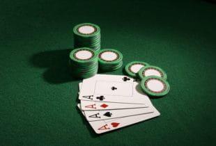 Die vier Ass-Spielkarten neben einem Stapel Pokerchips auf einem Tisch.