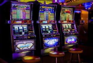 Verschiedene Slot-Automaten in einer Spielhalle nebeneinander.