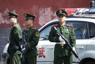 Drei bewaffnete chinesische Polizisten stehen vor einem Polizeiwagen.