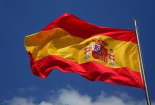 Spanische Flagge vor blauem Himmel und wenigen Wolken im Wind wehend.