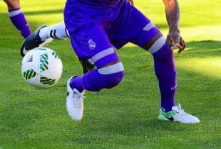 Fußballer von Real Madrid im blauen Dress im Dribbling auf dem Rasen.