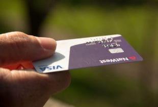 Eine Hand hält eine Kreditkarte in den Fingern.