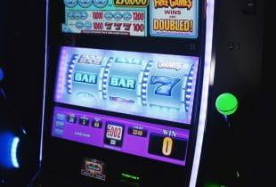 Glücksspielautomat im Dunkeln mit bunt und grell beleuchtetem Display.
