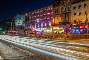 Bunt ausgeleuchtete Spielhalle und andere Geschäfte auf Hamburgs Reeperbahn bei Nacht.