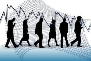 Sechs Silhouetten von entlassenen Mitarbeitern vor einem fallenden Aktienkurs.