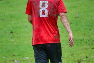 Die Rückseite eines Fußballspielers mit einem dreckigen roten Trikot mit der Nummer 8.