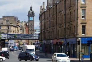 Eine Straße mit diversen Autos und Menschen in der Innenstadt von Glasgow.