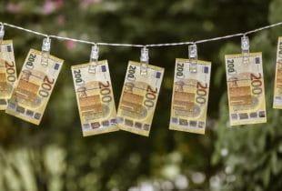 An einer Wäscheleine sind mehrere 200-Euroscheine mit Klammern befestigt.