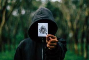 Eine Gestalt, dessen Gesicht man aufgrund einer übergezogenen Kapuze nicht erkennt, hält eine Pik-Ass-Spielkarte in der Hand.