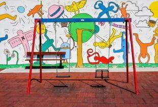 Eine bunte Schaukel vor einer bemalten Wand auf einem Spielplatz.