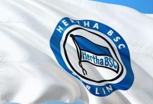 Flagge mit Logo von Hertha BSC im Wind unter blauem Himmel.
